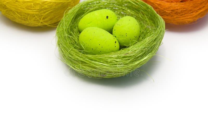 Huevos de Pascua multicolores en una jerarqu?a de mimbre en un fondo blanco fotografía de archivo