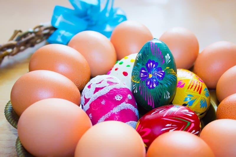Huevos de Pascua naturales y pintados a mano en la bandeja redonda fotografía de archivo
