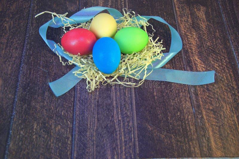 Huevos de Pascua pintados en una jerarquía de la paja en una mentira de la cinta azul en una tabla de madera fotos de archivo