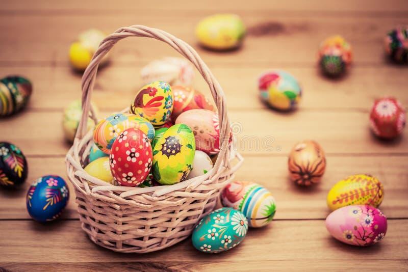 Huevos de Pascua pintados a mano coloridos en cesta y en la madera Decoración hecha a mano del vintage foto de archivo