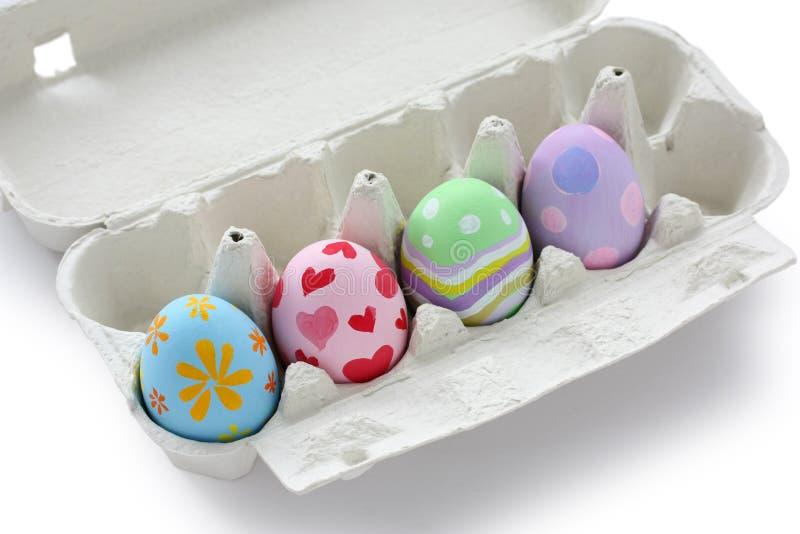 Huevos de Pascua pintados a mano en cartón de huevos imagen de archivo