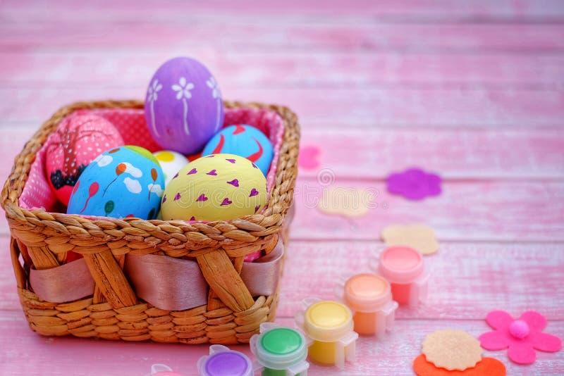 Huevos de Pascua pintados a mano en colores pastel con el fondo rosado fotografía de archivo