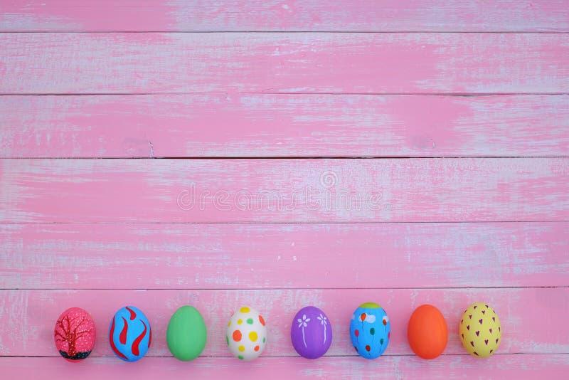 Huevos de Pascua pintados a mano en colores pastel con el fondo rosado imagen de archivo libre de regalías