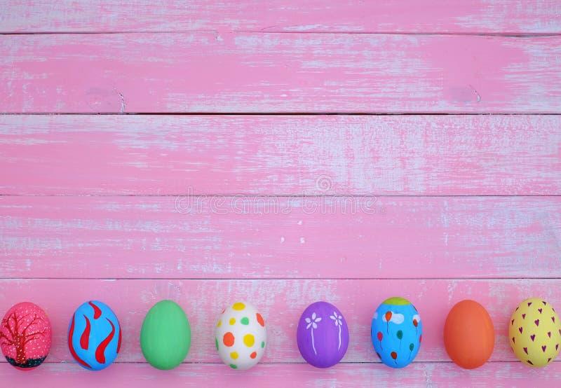 Huevos de Pascua pintados a mano en colores pastel con el fondo rosado foto de archivo libre de regalías