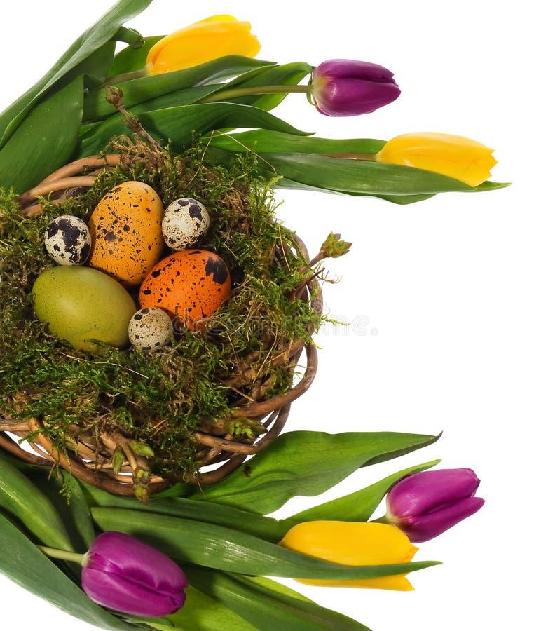 Huevos de Pascua pintados a mano en una guirnalda de mimbre, jerarquía del ` s del pájaro del musgo fotos de archivo
