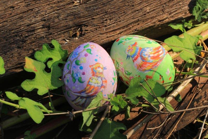 Huevos de Pascua pintados ocultados en la hierba, lista para el juego tradicional del juego de la caza del huevo de Pascua imagenes de archivo