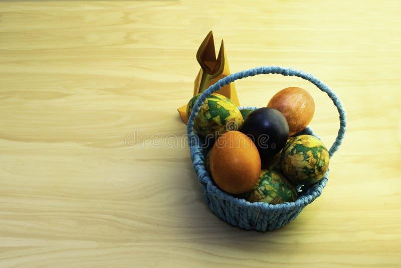 Huevos de Pascua que mienten en una cesta azul y un conejo de papel en una tabla de madera amarilla, copia-goma fotografía de archivo libre de regalías