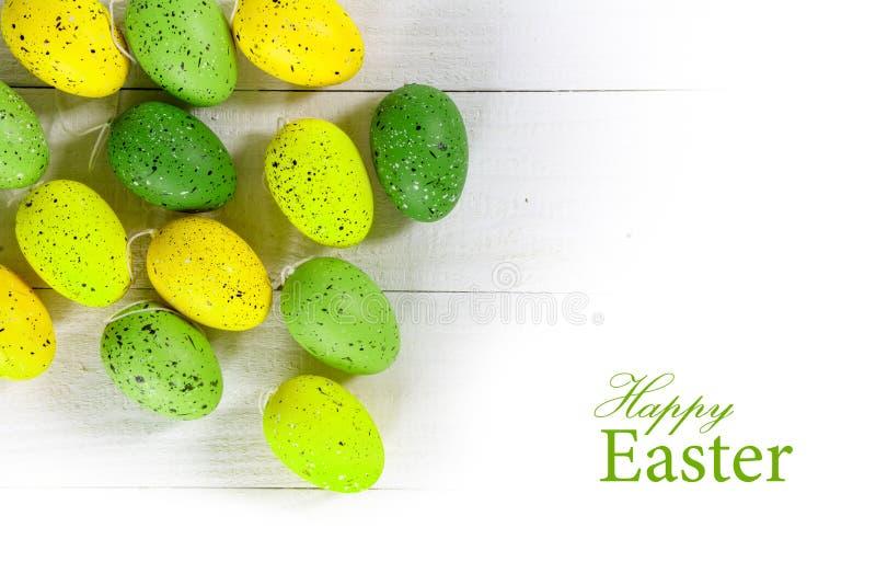Huevos de Pascua verdes y amarillos en la madera blanca, parte posterior aislada de la esquina fotos de archivo libres de regalías