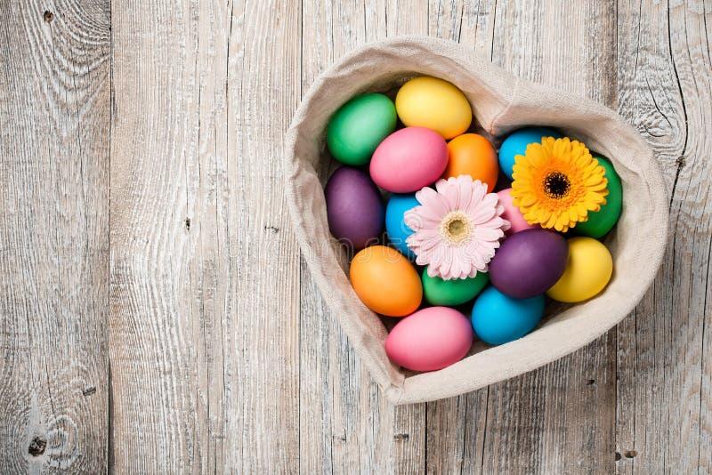 Huevos de Pascua y flores del gerbera en cesta en forma de corazón imágenes de archivo libres de regalías