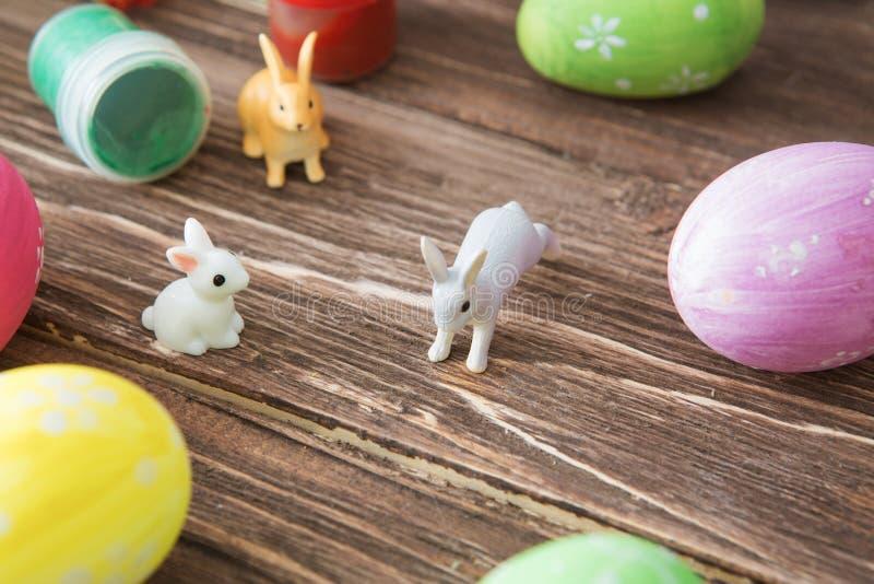 Huevos de Pascua y juguetes de los conejos de Pascua con la flor en la tabla de madera imagen de archivo