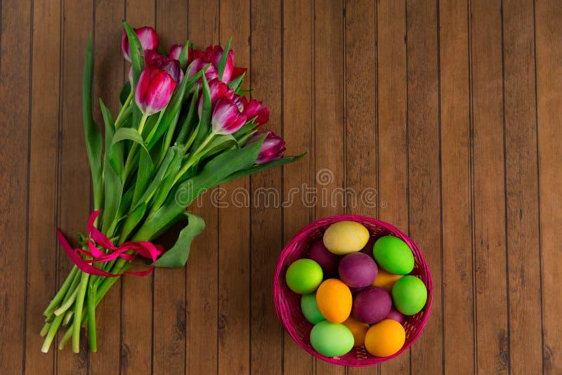 Huevos de Pascua y manojo pintados coloridos de tulipanes fotos de archivo libres de regalías