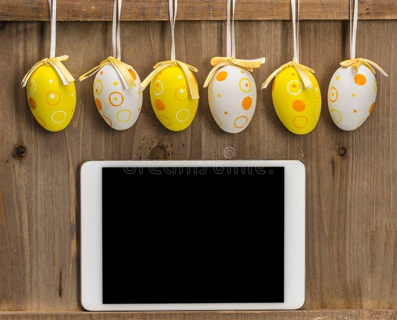 Huevos de Pascua y tableta vacía en blanco en un fondo de madera fotografía de archivo