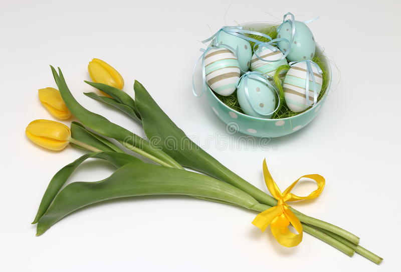 Huevos de Pascua y tulipanes amarillos foto de archivo