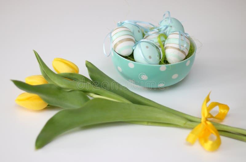 Huevos de Pascua y tulipanes amarillos fotografía de archivo