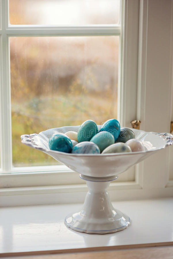 Huevos de piedra o de mármol en el soporte blanco al lado de una ventana fotos de archivo libres de regalías