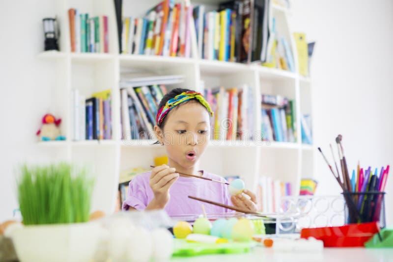 Huevos de pintura chocados de la niña para Pascua imagen de archivo libre de regalías