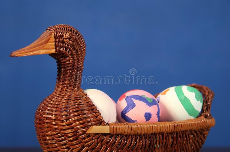 Huevos del color de Pascua en la cesta del pato cesta de mimbre de paja comida festiva en una tabla de madera oscura fotos de archivo