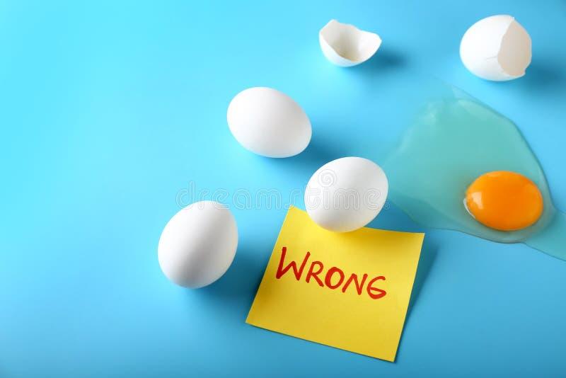 Huevos del pollo con uno agrietado y palabra MAL en la tarjeta de papel contra fondo del color Concepto del error fotos de archivo