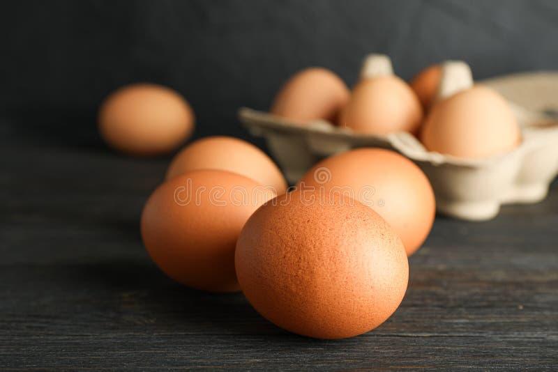 Huevos del pollo de Brown en caja del cartón en la tabla de madera contra el fondo negro, espacio para el texto fotos de archivo libres de regalías