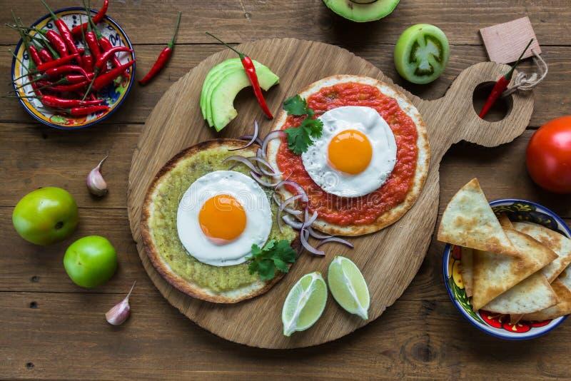 Huevos-divorciados, Spiegeleier auf Maistortillas mit Salsa verde und roja, mexikanisches Frühstück stockbild
