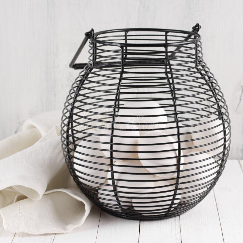 Huevos en cesta de alambre imagen de archivo