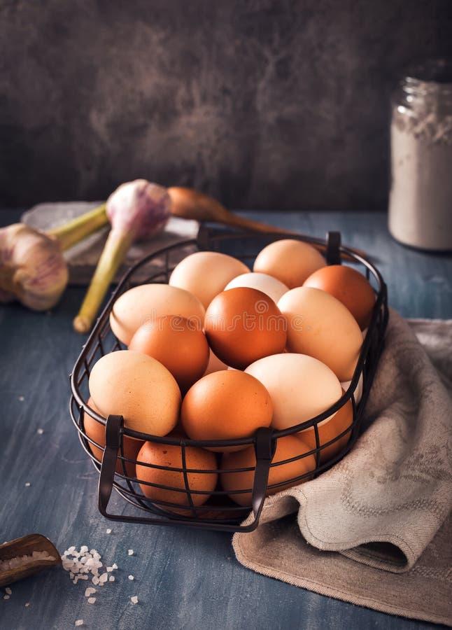 Huevos en cesta de alambre en la tabla rústica fotos de archivo