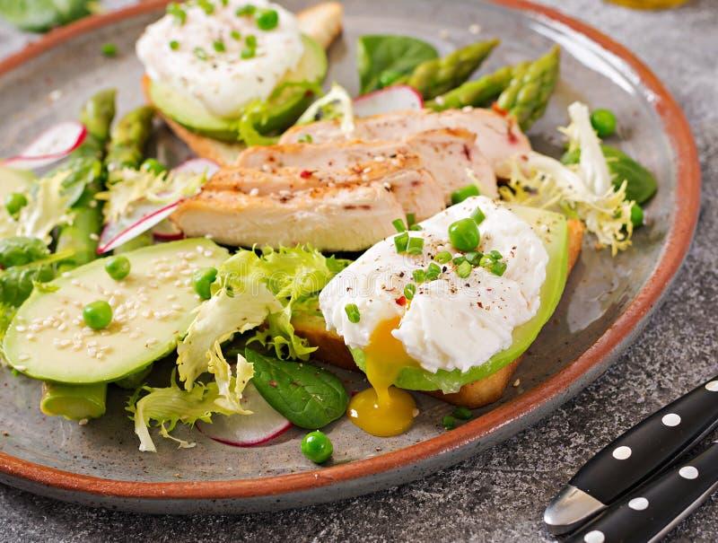 Huevos escalfados en tostada con el aguacate, el espárrago y el prendedero del pollo en parrilla imagen de archivo
