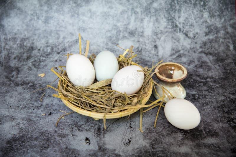 Huevos frescos de la granja Huevos blancos gallina Cesta de los huevos del pollo en paja en fondo concreto fotos de archivo libres de regalías
