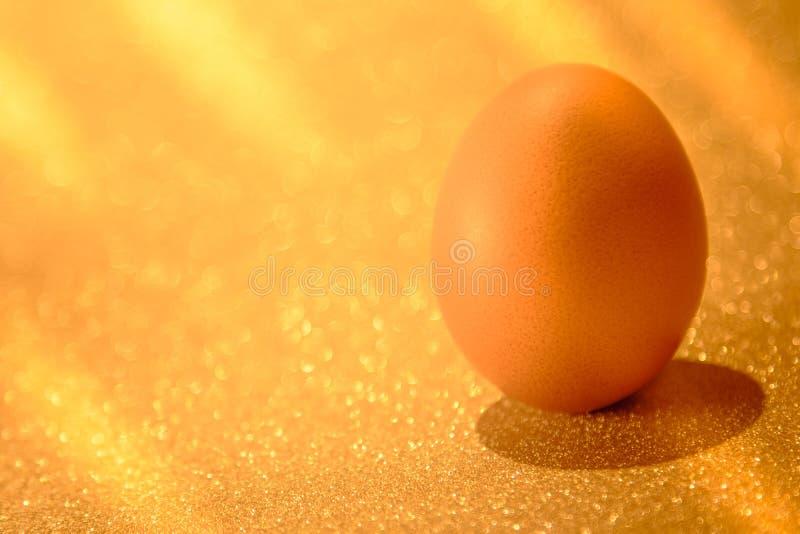 Huevos frescos en luz de oro del fondo de oro del bokeh H de oro foto de archivo