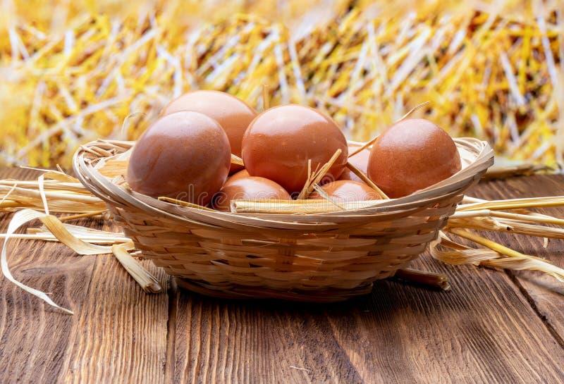 Huevos frescos y crudos en cesta de mimbre y paja fotos de archivo