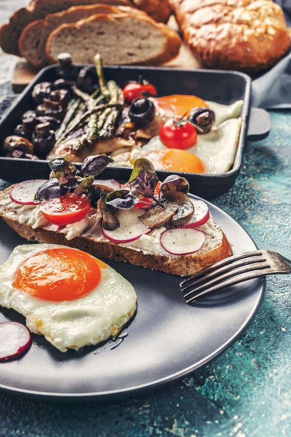 Huevos fritos, bocadillo con queso, setas, rábanos y verdes Tiro vertical del desayuno fotografía de archivo