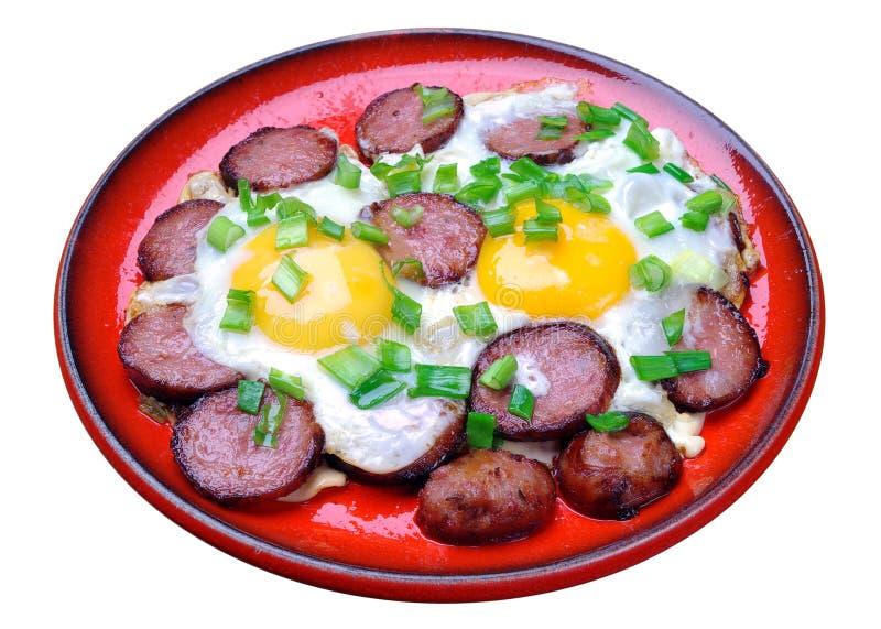 Huevos fritos con la salchicha en una placa roja imagen de archivo