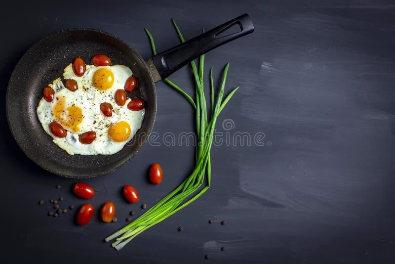 Huevos fritos con los tomates en una cacerola y cebollas frescas en fondo oscuro con el espacio para el texto Visión superior foto de archivo