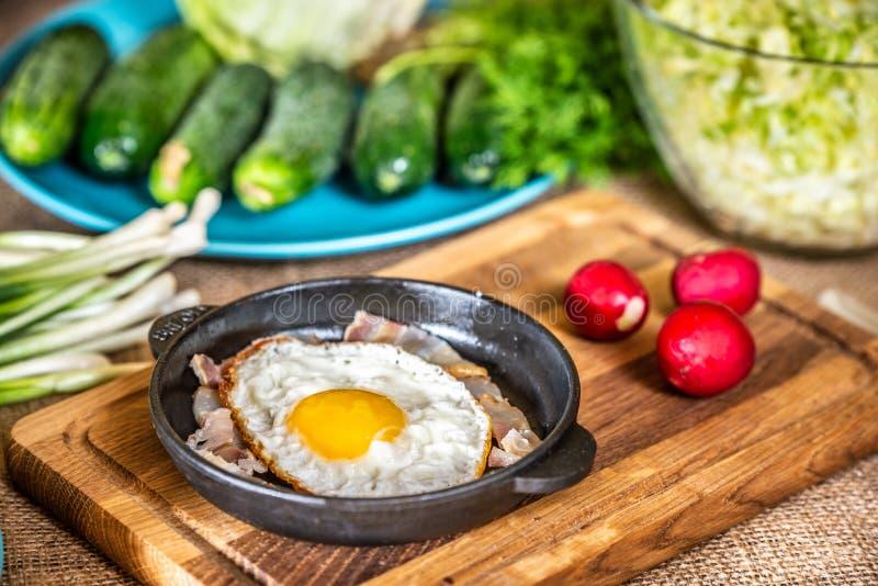 Huevos fritos con tocino en una cacerola imagen de archivo libre de regalías