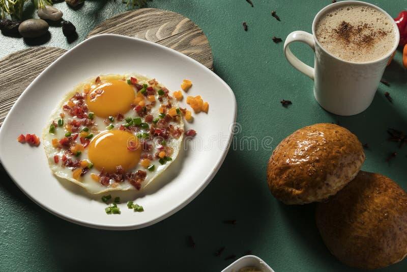 Huevos fritos con tocino, pepino rojo y pan y chocolate verdes en fondo verde fotografía de archivo