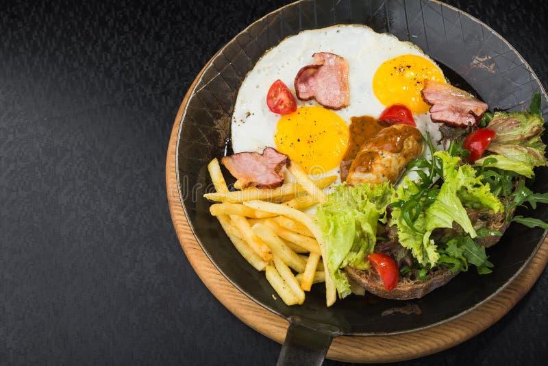 huevos fritos con tocino, salchichas, los tomates y la ensalada imagen de archivo