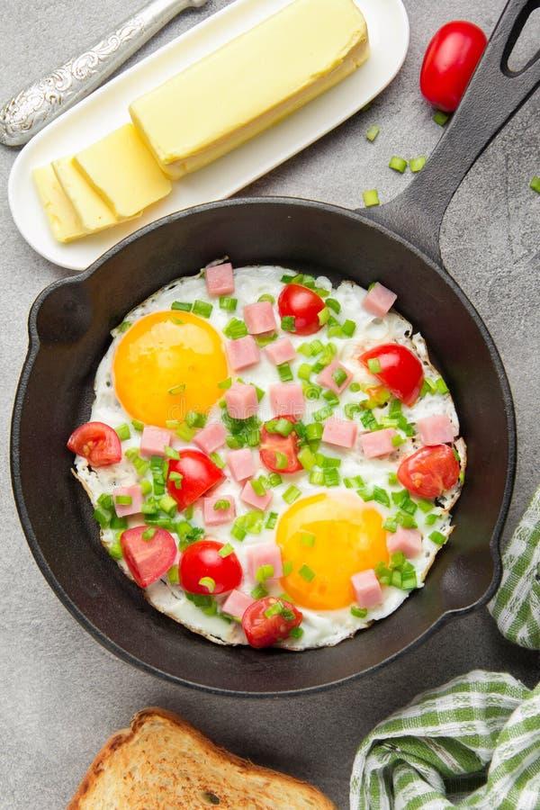 Huevos fritos en cacerola negra con el jam?n, los tomates de cereza y las cebollas verdes de la primavera Desayuno delicioso con  foto de archivo