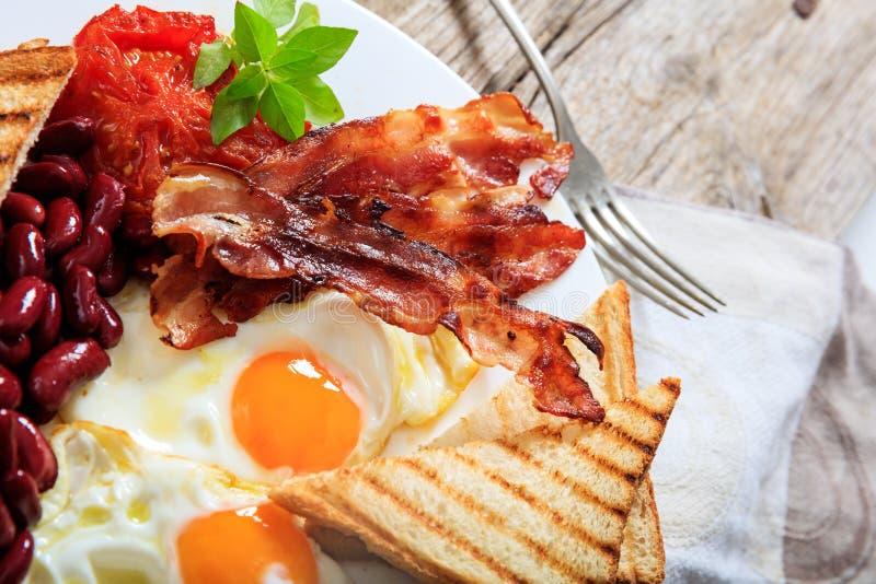 Huevos fritos, tocino y habas rojas del kindey imagen de archivo