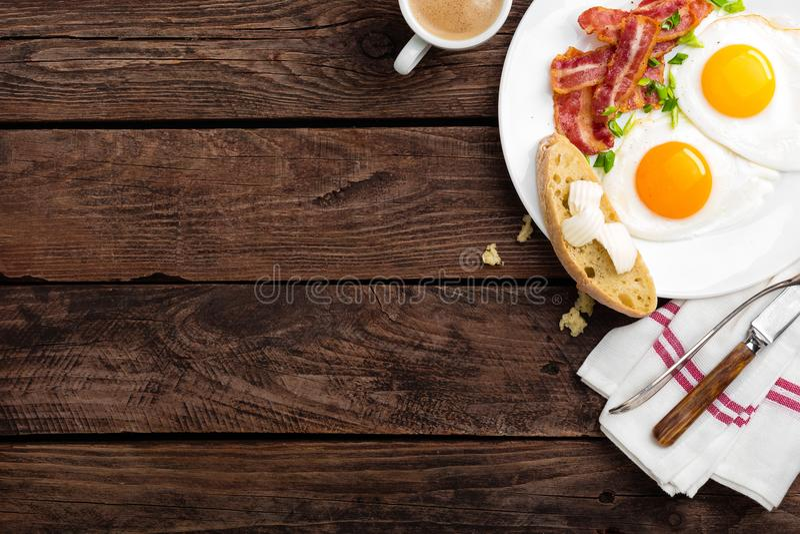 Huevos fritos, tocino y pan italiano del ciabatta en la placa blanca Taza de café Opinión superior del desayuno Fondo de madera imágenes de archivo libres de regalías