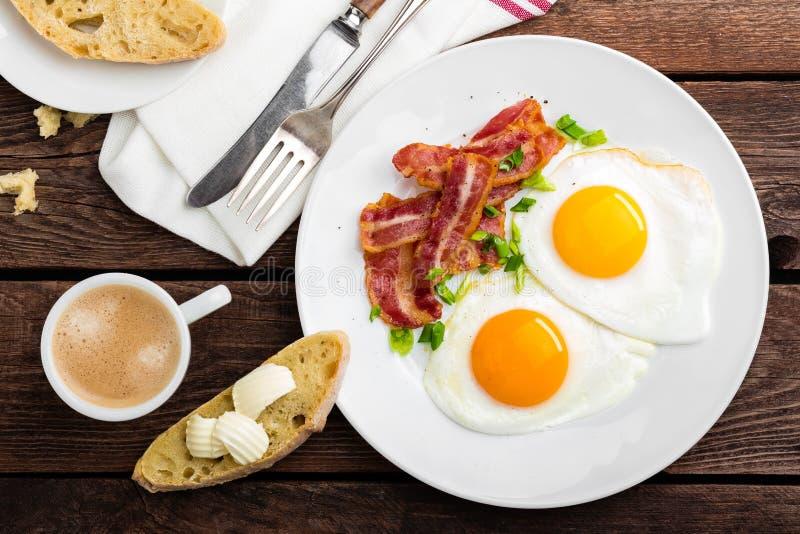 Huevos fritos, tocino y pan italiano del ciabatta en la placa blanca Taza de café Opinión superior del desayuno Fondo de madera imagen de archivo