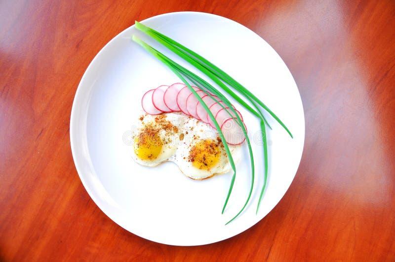 Huevos fritos y cebollas y rábanos en una placa imagen de archivo