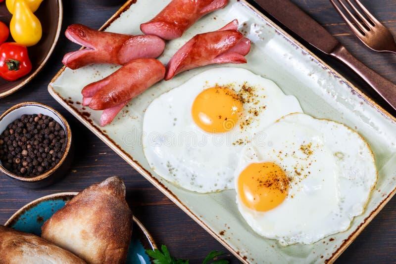 Huevos fritos y salchicha con pan y verduras frescas Desayuno caliente y sano, visión superior, endecha plana foto de archivo libre de regalías