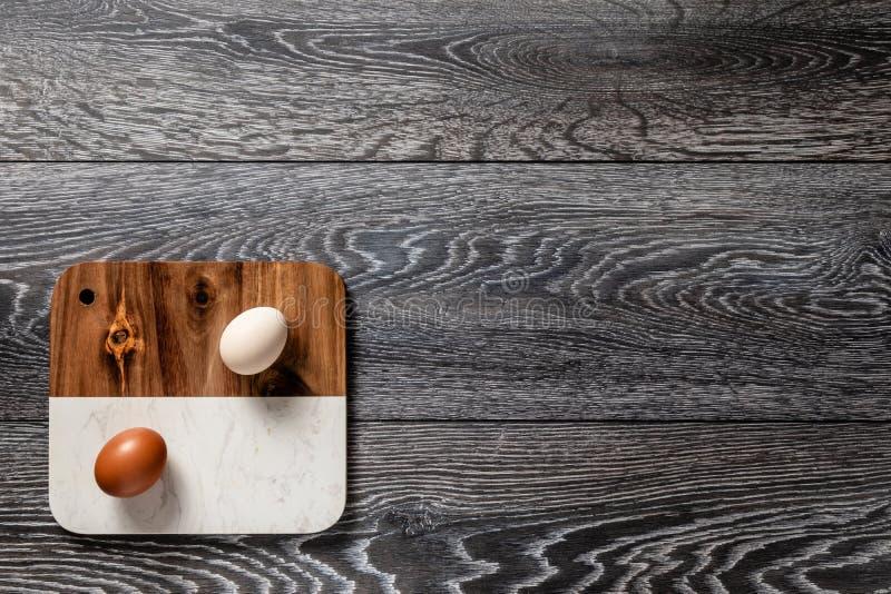Huevos grandes orgánicos frescos del marrón de la granja y blancos en cartón en la tabla oscura rústica del fondo de madera de ro fotos de archivo