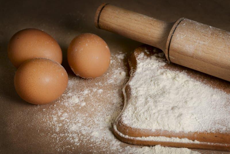 Huevos, harina y rodillo de los ingredientes que cuecen en la tabla fotos de archivo libres de regalías
