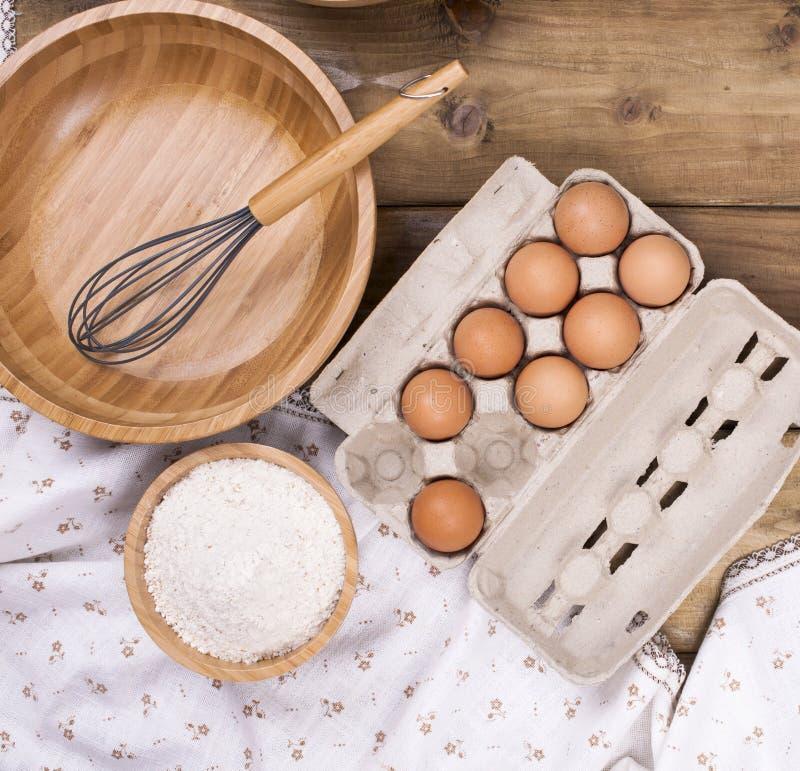 Huevos, harina y un cuenco de madera para hacer una pasta para una empanada con una cereza Pasteles hechos en casa del verano Vis foto de archivo libre de regalías