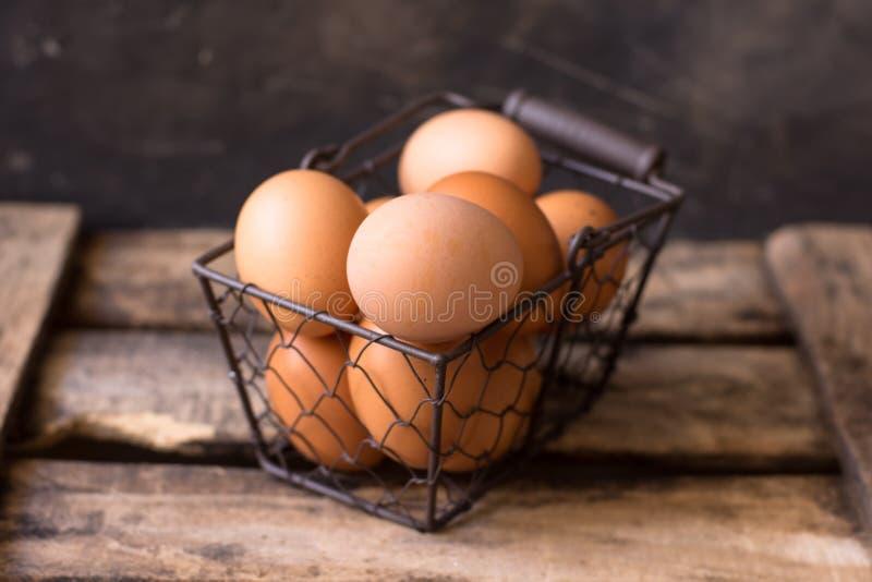 Huevos marrones frescos en una cesta de alambre en una caja de madera del vintage, fondo negro, Pascua imágenes de archivo libres de regalías