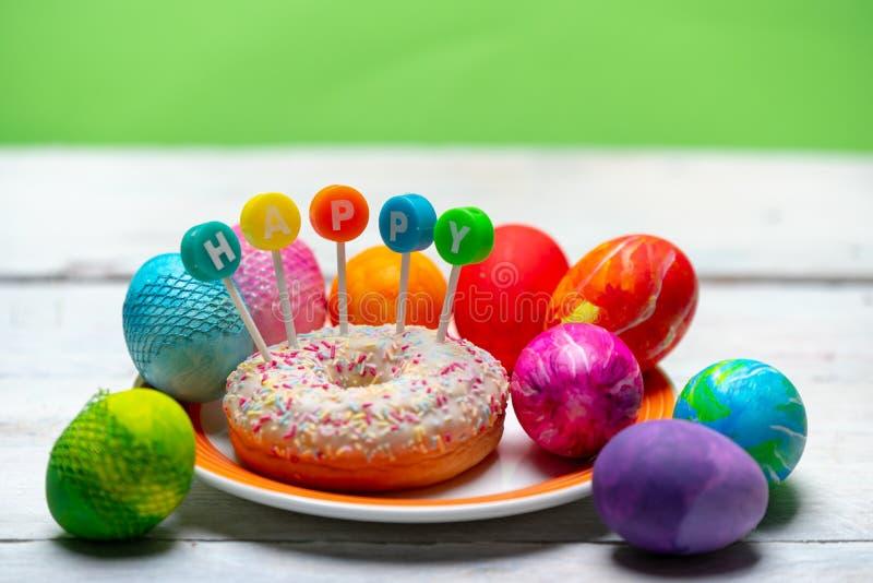 Huevos muy coloridos, brillantemente pintados al lado de un buñuelo colorido con la palabra FELIZ fotos de archivo libres de regalías