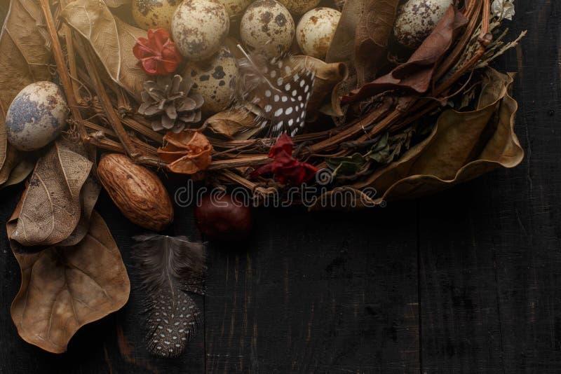 Huevos negros en una jerarqu?a de ramas secas en un tablero negro Estilo de Pascua foto de archivo