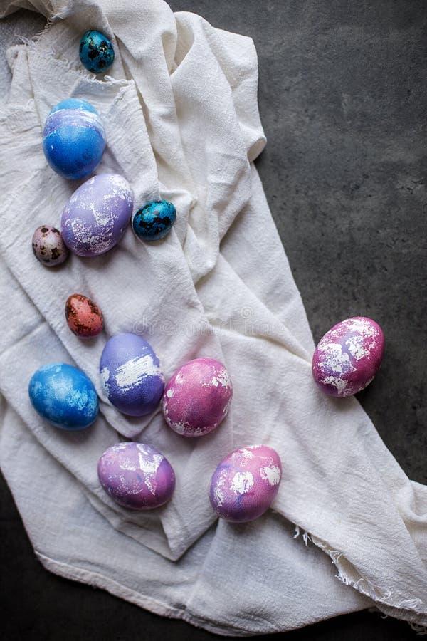 Huevos pintados coloridos del pollo de Pascua con la servilleta en fondo oscuro foto de archivo libre de regalías