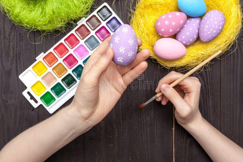 Huevos pintados a mano de Pascua del día de fiesta con el pollo en la tabla fotos de archivo libres de regalías
